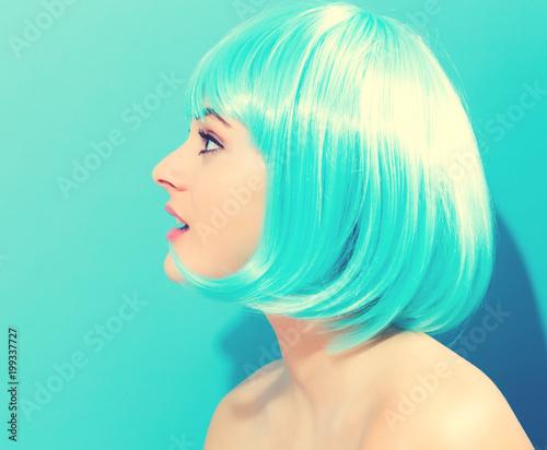 Foto op Plexiglas Kapsalon Beautiful woman in a bright blue wig on a blue background