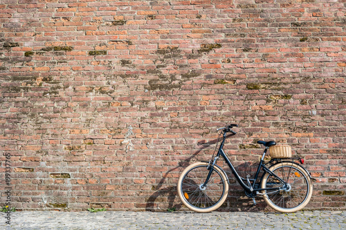 Foto op Plexiglas Fiets Black retro vintage bicycle with old brick wall.