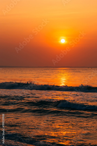 Foto op Plexiglas Oranje eclat orange sunrise on the sea with waves