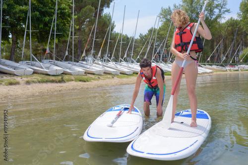 Fototapeta Couple setting off on windsurfing boards