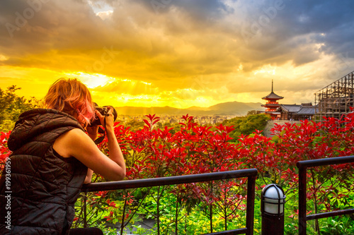 Fotobehang Kyoto Travel woman photographer with professional camera takes shot of Kiyomizu-dera Temple with red pagoda at sunset light in spring time. Scenic aerial cityscape of Kyoto, Japan. Asian traveler concept.