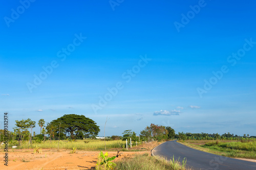 Foto op Aluminium Blauw Rural roads Beside with nature and tree big green in fluffy clouds with blue sky background.