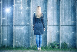 Back view of a business woman stands in front of the concrete wall with digital abstract cyberspace network background. - 199398183