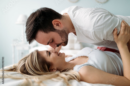 Portrait of young loving couple in bedroom - 199398780