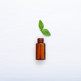 Bottle of essential oil with fresh basil leaves setup with flat lay on white wooden table. - 199401178