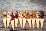 Concept for homemade various nuts ice cream. Mixed nuts in waffle cones on shabby wooden background.top view - 199405976