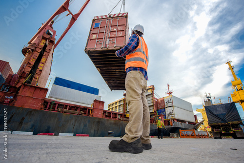 Fototapeta foreman takes control the operation lifting container from yard to accommodation in bay storage with report on line status of the opertation by device