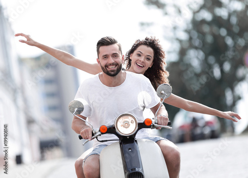 Happy young couple riding a scooter in the city on a sunny day