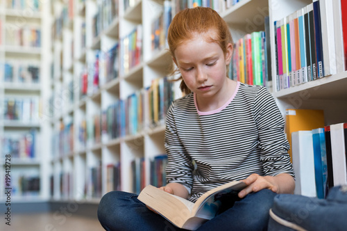 Cute girl reading book in library