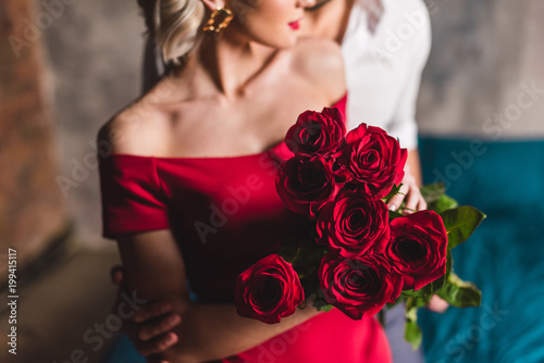 cropped shot of man embracing girlfriend in red dress holding beautiful roses