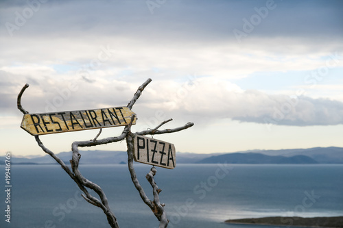 Canvas Pizzeria Restaurant and pizzeria signs on wooden boards in a remoted rural area in countryside, Titicaca Lake, Bolivia