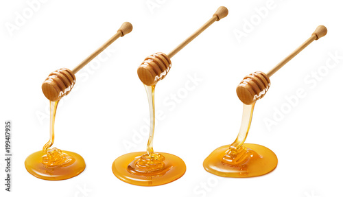 Foto Murales Set of wooden dippers with dripping honey isolated on white background