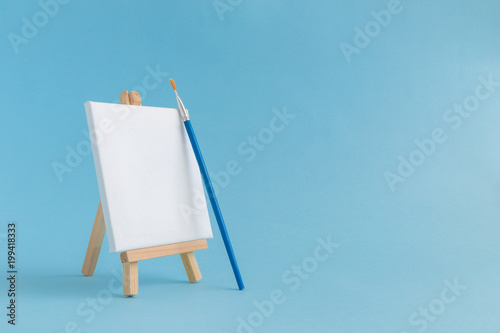 Blank art board canvas with wooden stand miniature and paintbrush on plain blue background. Art equipment minimalistic concept.