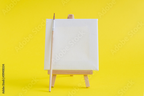Blank art board canvas with wooden stand miniature and paintbrush on plain yellow background. Art equipment minimalistic concept.