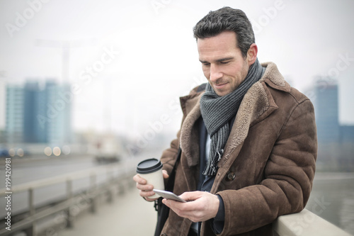 Handsome man walking in the street, checking his phone and drinking coffee