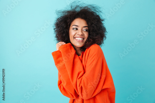 Colorful portrait of amazing woman in red shirt with afro hairstyle looking aside with smile pressing her arms to chest, isolated over blue background