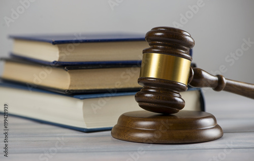 Wooden mallet used by a judge or at an auction next to a book. Concept