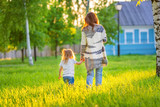 Mother and little daughter walking in spring sunny park - 199429331