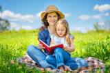 Mother and daughter enjoy reading book sitting on green meadow in the summer park - 199429745