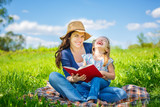 Mother and daughter enjoy reading book sitting on green meadow in the summer park - 199429783