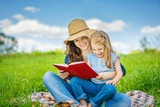 Mother and daughter enjoy reading book sitting on green meadow in the summer park - 199429798