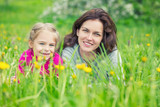 Mother and daughter lying on green summer grass with blooming yellow flowers - 199430138
