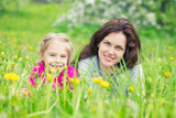 Mother and daughter lying on green summer grass with blooming yellow flowers - 199430153