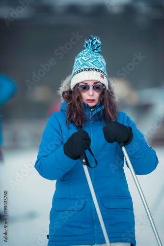 Fotobehang Bleke violet Wintersport woman in blue jacket and sunglasses holding ski poles.