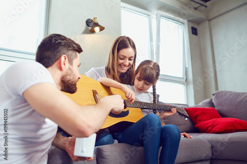 Foto Murales The family plays guitar together and sings songs. Mother, father and daughter spend time together.