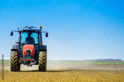 Fotobehang Trekker Tractor on the field spreading fertilizer in the early spring time. Fertilization of soil in the early spring time.