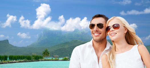 travel, tourism and summer holidays concept - happy couple in sunglasses at touristic resort over exotic bora bora island background
