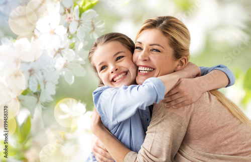 people and family concept - happy smiling mother hugging daughter over cherry blossom background - 199458370