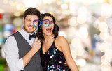 celebration, fun and holidays concept - happy couple posing with party glasses over lights background - 199458715