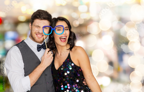 Foto Murales celebration, fun and holidays concept - happy couple posing with party glasses over lights background