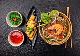 Asian shrimps soup with spring rolls and chopsticks. - 199459166