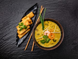 Asian kari soup with spring rolls and chopsticks. - 199459186
