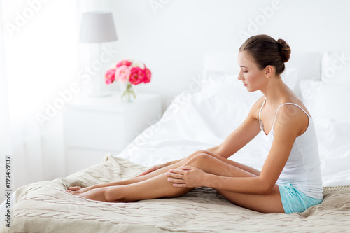 people, beauty, depilation, epilation and bodycare concept - beautiful woman touching smooth leg skin on bed at home bedroom - 199459137
