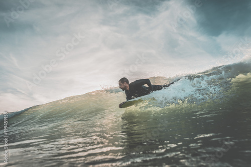 Fototapeta Youthful young man boogie boarding an ocean wave at sunset under a cloudy sky. Extreme water sports and outdoor active lifestyle. Vintage filter with soft style