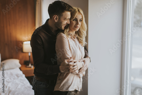 Loving couple by window in the room