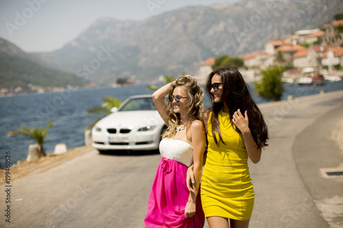 Two pretty young women by white cabriolet car