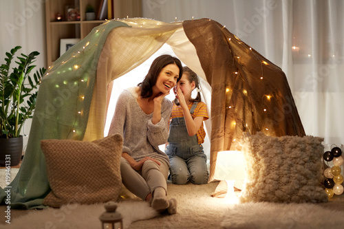 family, hygge and people concept - happy mother with little daughter whispering in kids tent at night at home