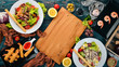 Assortment of food, salads with shrimp and meat. On a wooden background. Top view. Copy space for your text.