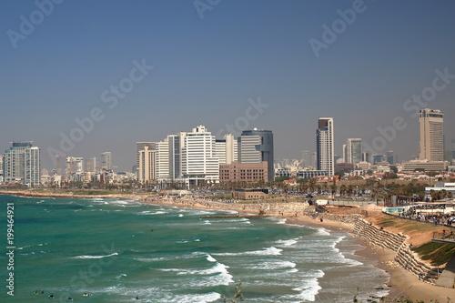 Malowniczy widok zatoki Morza Śródziemnego, plaża, nabrzeżę i nowoczesna architektura w Tel Awiwie, Izrael, na piaszczystej plaży odpoczywający ludzie, fale na morzu, niebieskie niebo