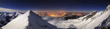 Night winter panorama in High Mountains with sparkling lights in the background