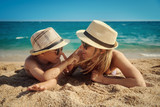 Young mom and son in sunglasses are having fun on the beach against the sea. They are touching the noses of each other.