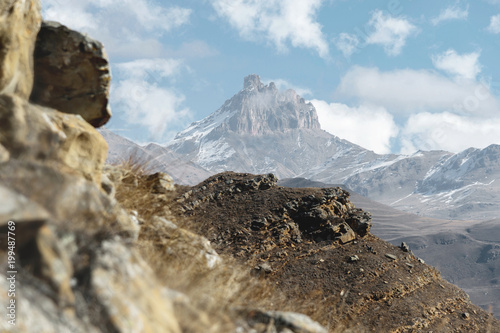 Autumn mountain landscape of yellowed slopes and grass in the mountains with epic rocks and parts of snow-covered slopes on a sunny day against the blue sky and white clouds. The concept of ideal - 199487769