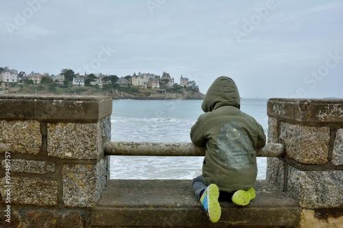 Un enfant qui regarde la mer à Dinard en Bretagne