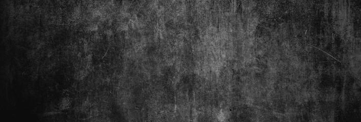 Textur einer fast schwarzen und alten Betonwand als Hintergrund, auf die leichtes Licht fällt