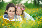 Mother and daughter lying on spring meadow enjoy reading book - 199498788