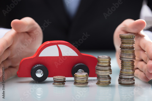 Businessman Protecting Car And Stacked Of Coins - 199508737